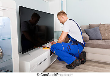 Male Electrician Fixing Television - Young Male Electrician ...