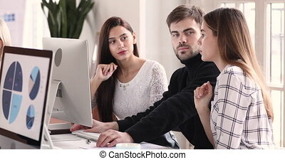 Smart young male employee helping two smiling female colleagues with computer software at modern workplace. Happy three millennial coworkers involved in project daily working routine in office.