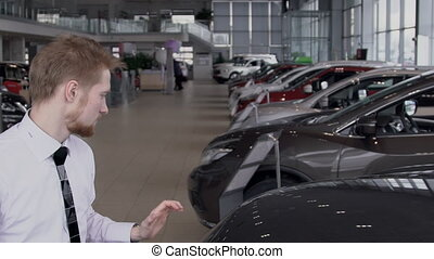 Young male employee is closing hood of car, standing in auto salon, bearded guy in work process in modern automobile center with rows of new cars. slow motion.
