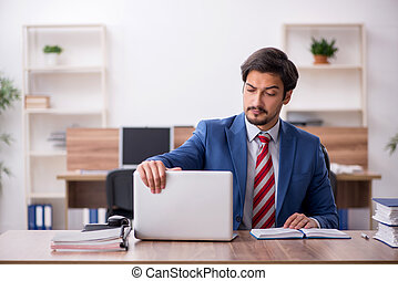 Young male employee sitting at workplace