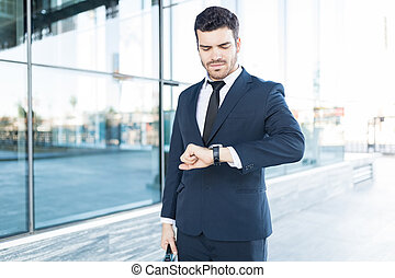 Young Male Executive Tracking Time On Watch