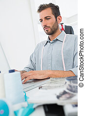 Young male fashion designer using laptop