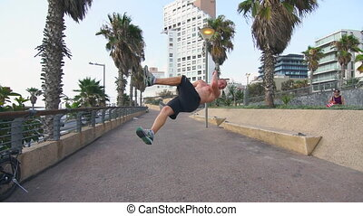 Young male free runner performing flips on alley at sunny...