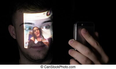 Young male freelancer searching people on social media using his smartphone while the images are projected on his face