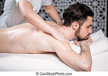 young male getting massage for arms in modern resort. -...