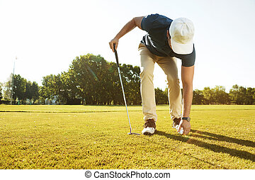 Young male golfer placing golf ball on a tee while playing...