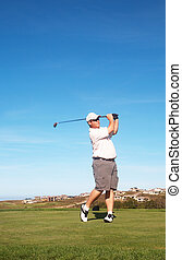 Young male golfer playing off the tee box