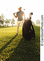 Young male golfer standing on a green field