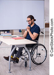 Young male handicapped student in the classroom