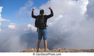Young male hiker with backpack jumping on the edge of the mountain and victoriously raising hands up. Man enjoying freedom during summer travel. Cloudy sky at background. Rear back view Slow motion