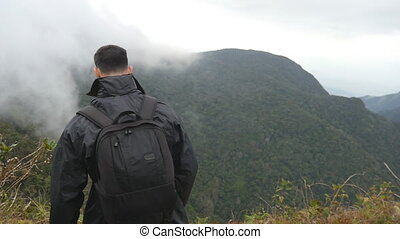 Young male hiker with backpack reaching up top of mountain and raised hands. Man tourist standing on the edge of beautiful canyon, victoriously outstretching arms up. Slow motion Rear back view