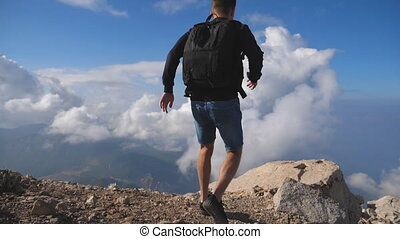 Young male hiker with backpack reaching up top of mountain with cloudy sky at background and raising hand. Man tourist standing on edge of the hill and victoriously outstretching arm. Slow motion