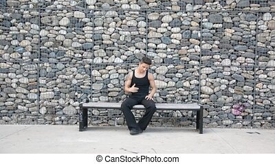 Young male hip-hop dancer dancing on bench