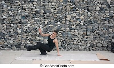 Young male hip-hop dancer dancing outside