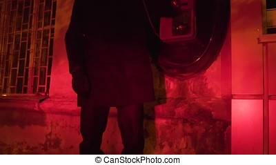 Young male in the city at night using payphone. Footage....