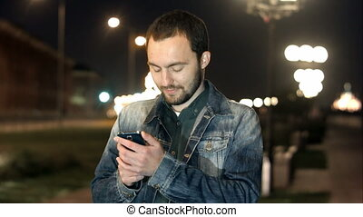 Young male in the city using his smartphone.