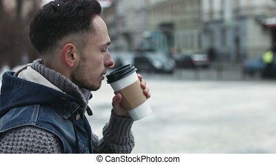 Young male is drinking takeaway coffee outdoors and waiting for someone. Attractive man sipping coffee in the city center while looking forward to meet his friend.