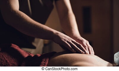 Young male massage therapist does back massage to a woman ...
