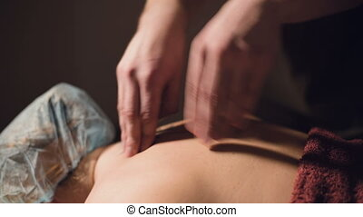 Young male massage therapist is doing finger massage of a ...