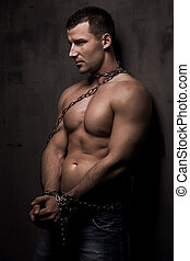 young male model well build with chains over his body