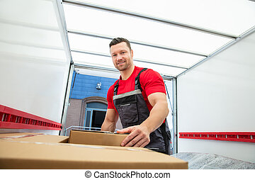 Young Male Mover Arranging The Boxes Inside The Van