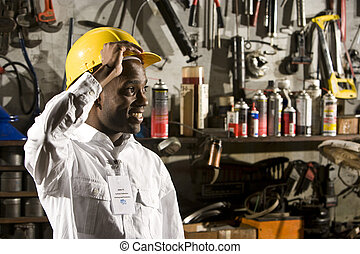 Young male office worker in repair shop - Young African...