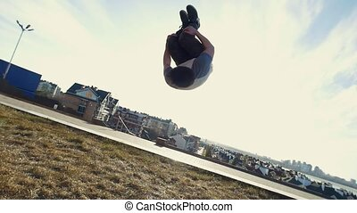 Young male Parkour tricker jumper performs amazing flips,...