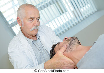 young male patient having neck examined by medical physician