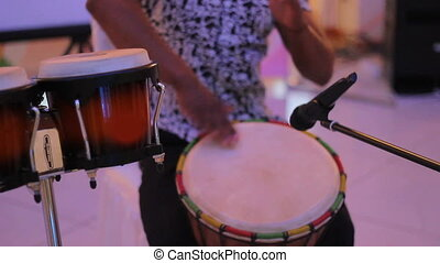 Hand of male percussionist playing cuban drums against black background