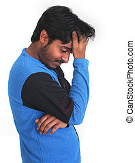 Young male person in gloomy mood with head on hands and...