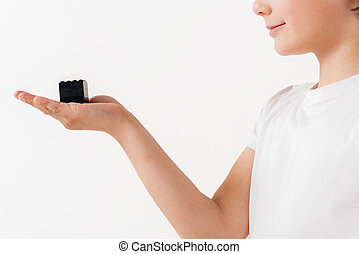 Little boy is presenting small lego-cube on his palm. Isolated
