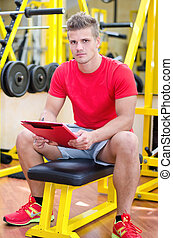 Young male personal trainer holding clipboard