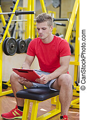 Young male personal trainer reading from clipboard
