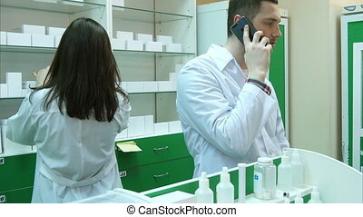 Young male pharmacist talking on mobile phone while checking prescription in pharmacy
