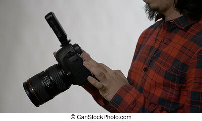 Young male photographer with beard checking and deleting the...