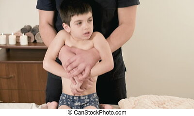 Young male physiotherapist masseur doing therapeutic stretching of the back and spine to a small child in a massage room
