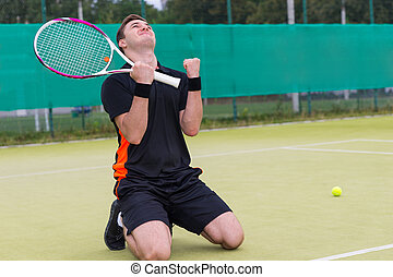 Young male player fell on his knees and made a fist because of the win in tennis match
