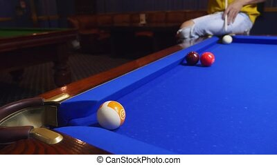young male professional pool player performing tricks while playing billiards