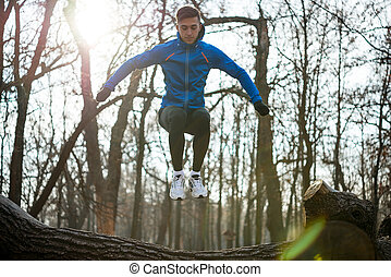 Young Male Runner Jumping on the Log in the Park in Cold Sunny Autumn Morning. Healthy Lifestyle and Sport Concept.