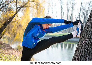 Young Male Runner Stretching in the Park in Cold Sunny Autumn Morning. Healthy Lifestyle and Sport Concept.