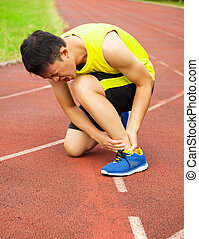 young male runner with ankle injury on track