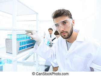 Young male scientist looking at a sample in a test tube side...