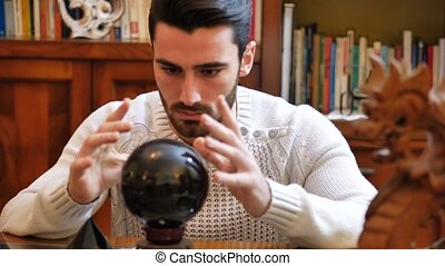 Handsome young man predicting the future by looking into black crystal ball
