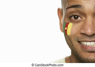Young Male Sports Fan With Cameroon Flag Painted On Face