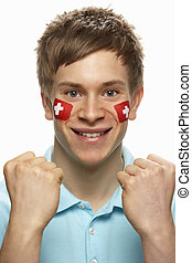 Young Male Sports Fan With Swiss Flag Painted On Face