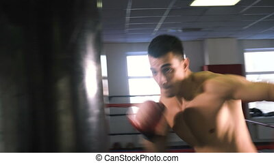 Young male sportsman athlete training in boxing gym