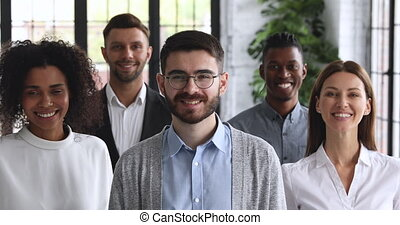 Young male startup owner with business team looking at camera