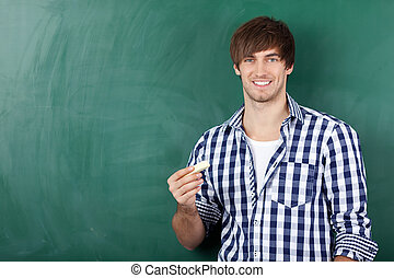 Young Male Student In Front Of Chalkboard