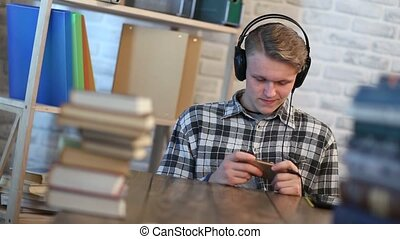 Young male student reading text message on phone