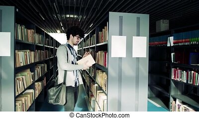 Young male student studying in a library.